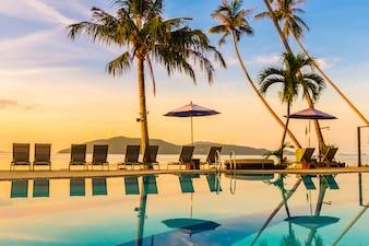 Bela vista ao ar livre com guarda-chuva e cadeira ao redor da piscina em hotel de luxo
