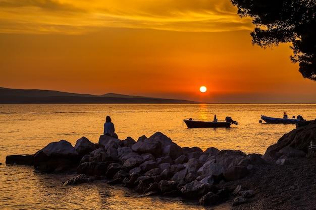 Bela vista com a mulher sentada nas pedras e observando o pôr do sol, croácia