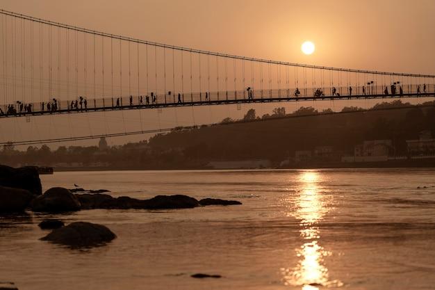 Bela vista da água do rio ganges e da ponte ram jhula ao pôr do sol