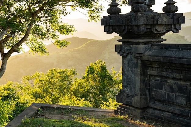 Bela vista da antiga construção arquitetônica com árvores verdes e colinas na foto de fundo