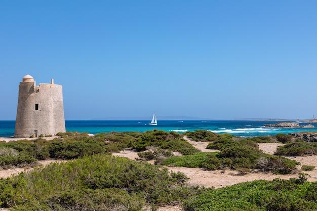 Bela vista da antiga torre de observação torre de ses portes e iate à vela. ilha de ibiza. espanha