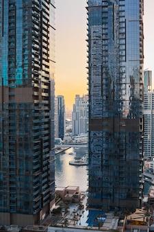 Bela vista da arquitetura do arranha-céu de vidro no contexto do pôr do sol e da cidade moderna