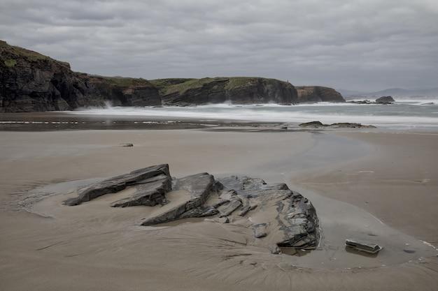 Bela vista da bela praia de os castros em um dia nublado em ribadeo, galiza, espanha