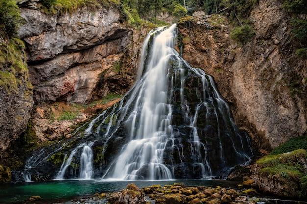 Bela vista da famosa gollinger wasserfall com rochas cobertas de musgo e árvores verdes