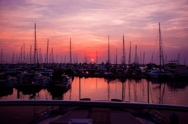 Bela vista da marina e do porto com iates e barcos a motor. pôr do sol no oceano.