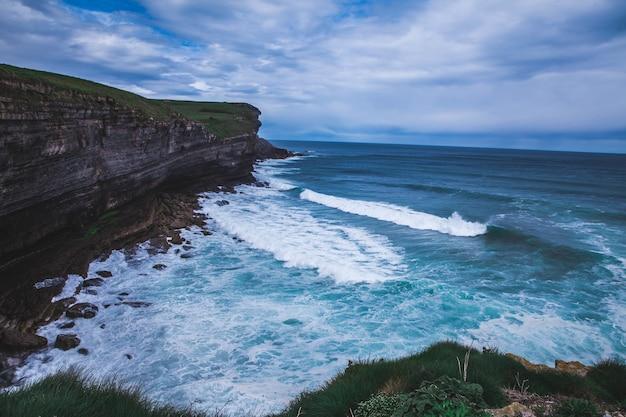 Bela vista da onda de espuma na costa perto do penhasco