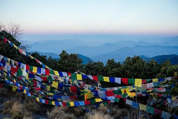 Bela vista da paisagem das montanhas do himalaia. topos de montanhas cobertas de neve e bandeiras tibetanas de oração multicoloridas. conceito de trekking nas montanhas