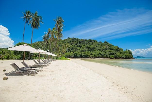 Bela vista da paisagem de espreguiçadeiras na praia tropical, o mar esmeralda e a areia branca contra o céu azul