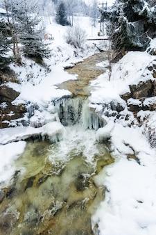 Bela vista da pequena cachoeira no rio da montanha no inverno