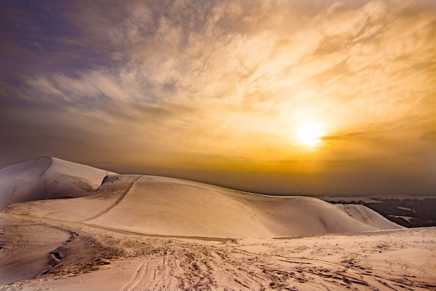 Bela vista da pista de esqui em uma noite ensolarada de inverno no fundo do céu nublado