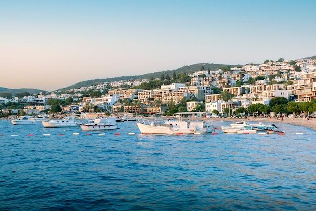 Bela vista da praia de bodrum, veleiros, iates e hotéis ao pôr do sol