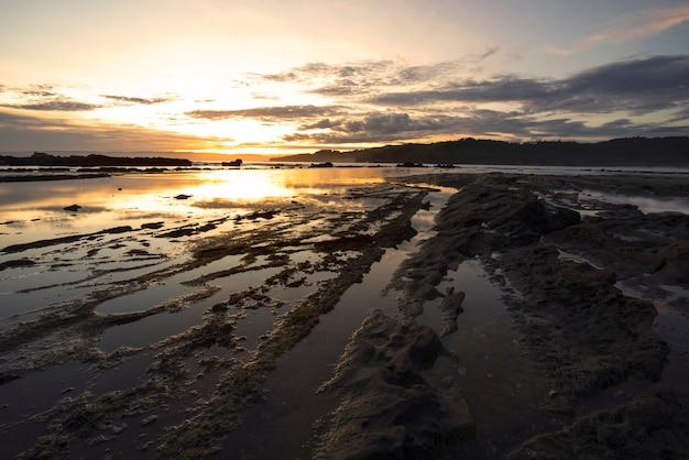 Bela vista da praia de sawarna com pedras e ondas calmas