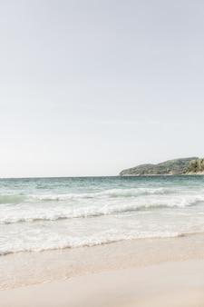 Bela vista da praia tropical com areia branca, mar azul com ondas e ilha verde no horizonte em phuket