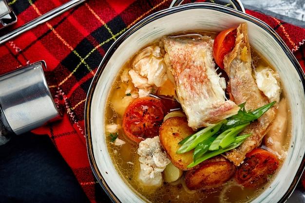 Bela vista da sopa de peixe em um prato branco, sobre um fundo de pedra, vista superior.