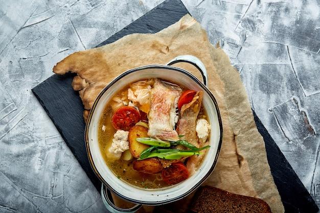 Bela vista da sopa de peixe em um prato branco, sobre um fundo de pedra