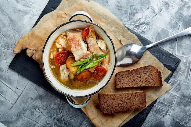 Bela vista da sopa de peixe em um prato branco