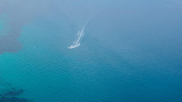 Bela vista da superfície do mar azul com passagem de pequeno navio da famosa rocha de penon de ifach, espanha. fundo natural.