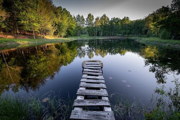 Bela vista das árvores em cores de outono refletindo em um lago com um calçadão de madeira