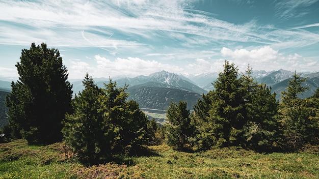 Bela vista das colinas cobertas de árvores sob as nuvens de tirar o fôlego no céu