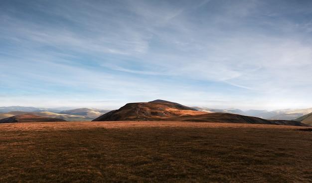 Bela vista das colinas nos campos de grama, sob o céu nublado. paisagem de fundo