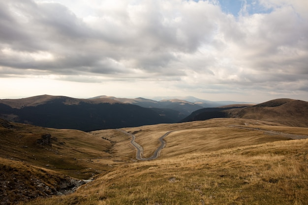 Bela vista das colinas nos campos de grama, sob o céu nublado.