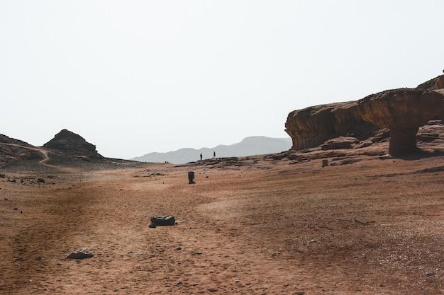 Bela vista das grandes rochas e dunas em um deserto com as montanhas ao fundo