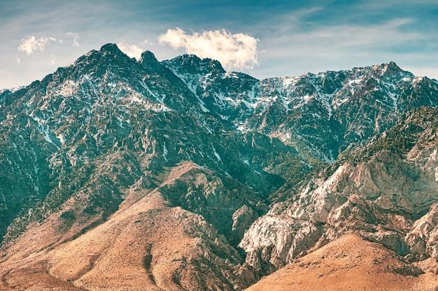 Bela vista das montanhas cobertas de neve sob um céu nublado de tirar o fôlego
