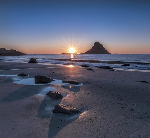 Bela vista das pedras na praia à beira-mar sob um incrível pôr do sol no céu
