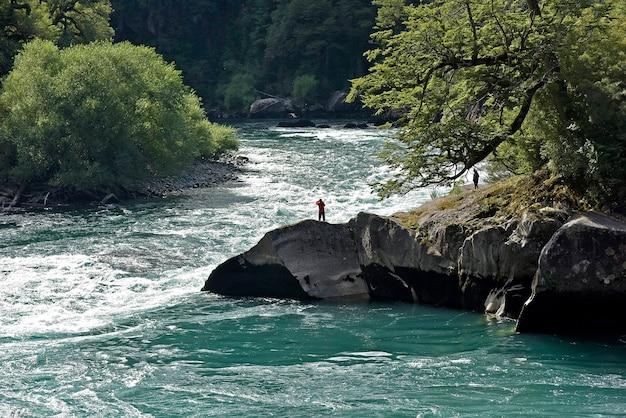 Bela vista das pessoas perto da margem de um rio cercado por árvores
