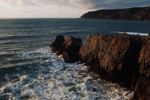 Bela vista das rochas ao pôr do sol com o mar ao fundo
