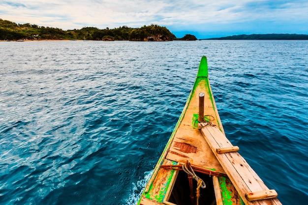 Bela vista de águas calmas e em terra capturada de um pequeno barco de madeira