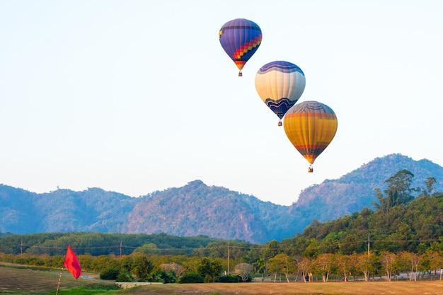 Bela vista de balão de ar quente no pôr do sol colorido acima das árvores ao lado das montanhas