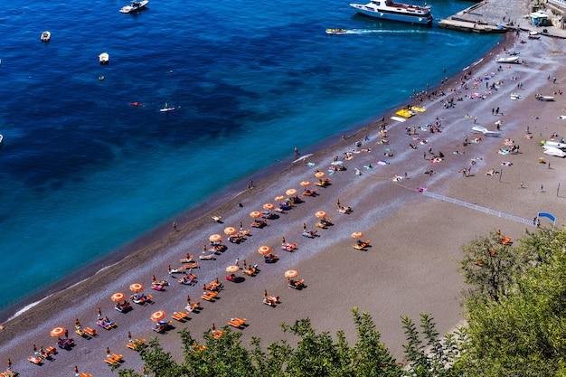 Bela vista de cima na praia e pessoas relaxando à beira-mar