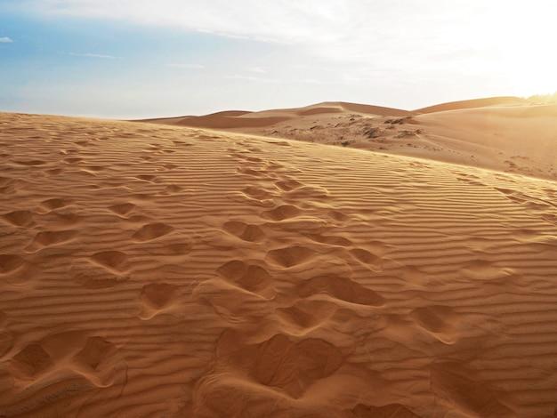 Bela vista de dunas de areia com textura de impressões. pegada passando por dunas de areia.