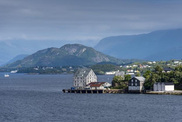 Bela vista de edifícios na costa perto de alesund, noruega com altas montanhas