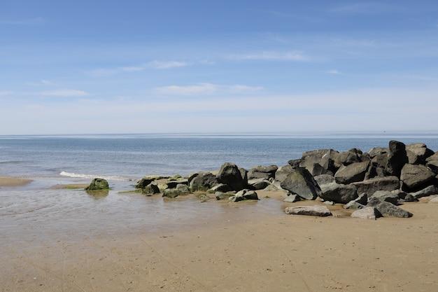 Bela vista de pedras na costa de um mar sob a luz