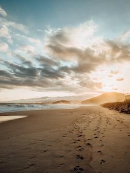 Bela vista de pegadas na areia durante o pôr do sol na praia do rio de janeiro