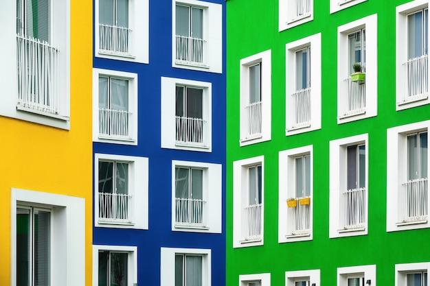 Bela vista de prédios de apartamentos em cores vivas com janelas com moldura branca em um dia frio
