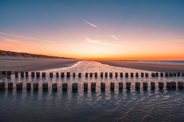 Bela vista de toras de madeira na água na praia capturada em oostkapelle, holanda