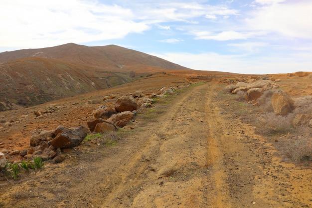 Bela vista de um caminho árido com colinas em fuerteventura, nas ilhas canárias