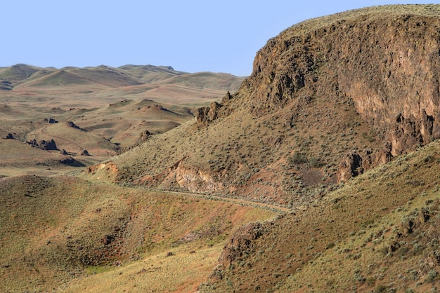 Bela vista de um caminho no lado da montanha com colinas e um céu azul em segundo plano