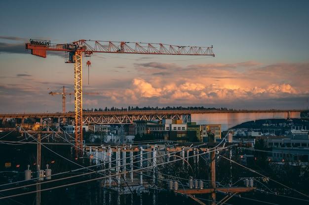 Bela vista de um canteiro de obras em uma cidade durante o pôr do sol