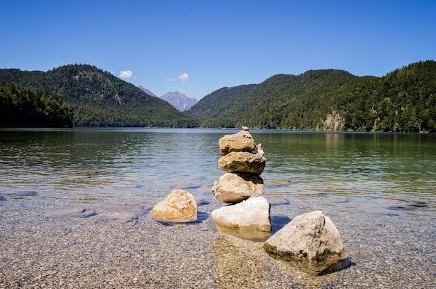 Bela vista de um lago com águas turquesas e um monte de pedras