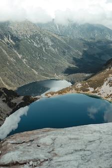 Bela vista de um lago rodeado de vegetação e montanhas