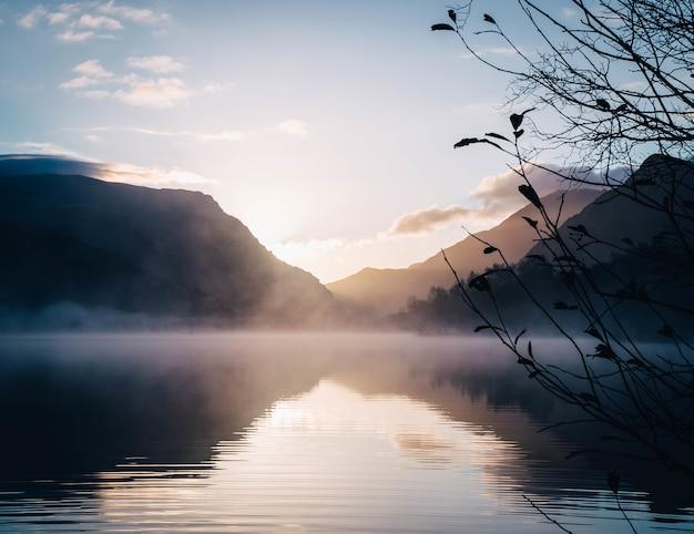 Bela vista de um lago rodeado por montanhas com um sol brilhante ao fundo
