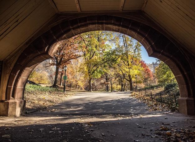 Bela vista de um parque de outono através de um arco de pedra
