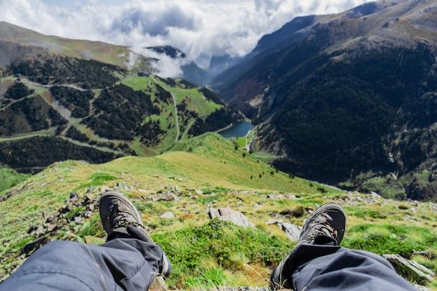 Bela vista de um vale de uma pessoa sentada acima das nuvens