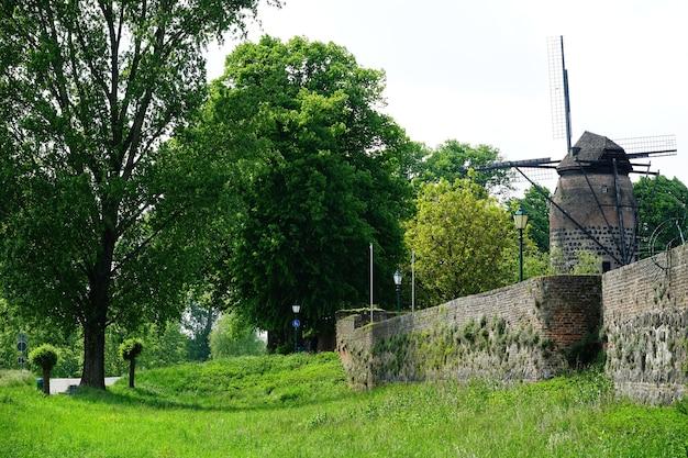 Bela vista de um velho moinho de vento cercado por grama e árvores em um parque
