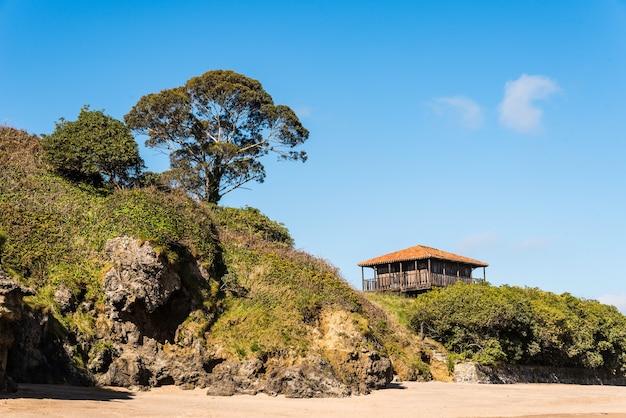 Bela vista de uma casa velha perto da praia cercada por árvores e grama sob um céu azul