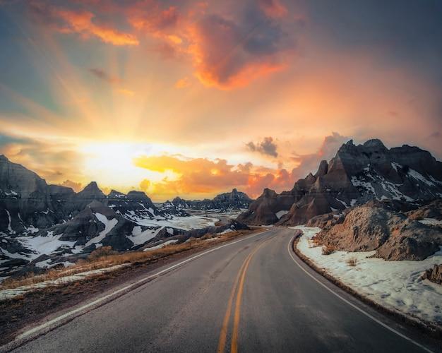 Bela vista de uma estrada rural estreita com montanhas rochosas cobertas de neve ao longe